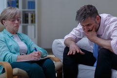 Therapist analysing problem of patient. Picture of female therapist analysing problem of despair patient stock images