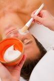 Therapist applying cream man's face Stock Photo