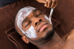Therapist Applying Face Mask To Man. Therapist Applying Face Mask To Young African Man In Spa Stock Images