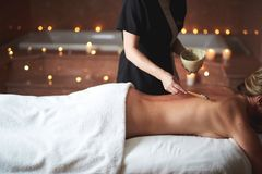 Therapist applying healthy spa mud to young lady royalty free stock photography