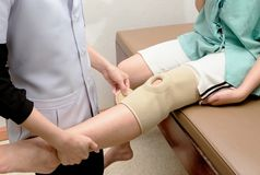 Therapist applying knee support to patient knee,rehabil stock image