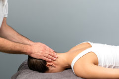 Therapist applying pressure on back of female head. royalty free stock image