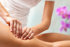 Therapist applying pressure with hands on upper thigh. Stock Photography