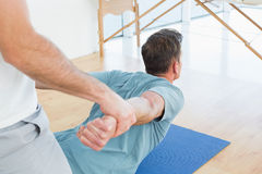 Therapist assisting man with stretching exercises. Physical therapist assisting young men with stretching exercises in the gym hospital Royalty Free Stock Image