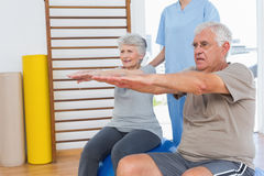 Therapist assisting senior couple with exercises Royalty Free Stock Photography