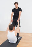 Therapist assisting young man with stretching exercises. Full length of a physical therapist assisting young men with stretching exercises in the gym hospital Stock Photography