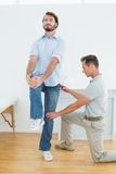 Therapist assisting young man with stretching exercises. Male therapist assisting young men with stretching exercises in the medical office Stock Photo