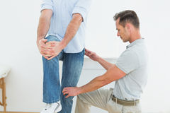 Therapist assisting young man with stretching exercises. Male therapist assisting young men with stretching exercises in the medical office Stock Photos