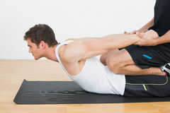 Therapist assisting young man with stretching exercises. Side view of a physical therapist assisting young man with stretching exercises in the gym hospital Royalty Free Stock Image
