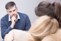 Therapist can help you find peace after family tragedy. Male therapist listening to his patients after family tragedy Stock Images
