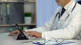 Therapist checks electronic medical records on tablet, technologies, healthcare. Stock photo stock images