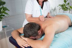 Therapist in chinese medicine working on the back of a  man Royalty Free Stock Image