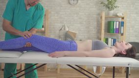 Therapist chiropractor treats the injured knee athletes female patient