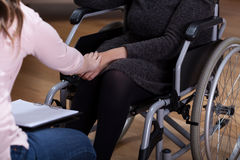 Therapist comforting disabled woman. Horizontal view of therapist comforting disabled woman Stock Image