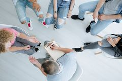 Therapist and difficult teenagers. High angle of therapist with notebook consulting with difficult teenagers Stock Image