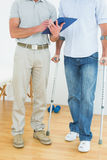 Therapist and disabled patient with reports. Low section of a male therapist and disabled patient with reports in the gym at hospital Royalty Free Stock Image