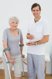 Therapist and disabled senior patient with reports. Portrait of a male therapist and disabled senior patient with reports in the gym at hospital Stock Photos