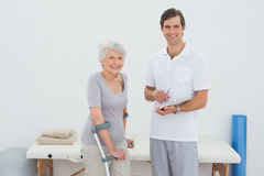 Therapist and disabled senior patient with reports Royalty Free Stock Photo