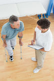 Therapist discussing reports with a disabled patient in gym hospital. High angle view of a male therapist discussing reports with a disabled patient in the gym Royalty Free Stock Photos