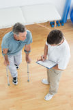 Therapist discussing reports with a disabled patient in gym hospital. High angle view of a male therapist discussing reports with a disabled patient in the gym Stock Images