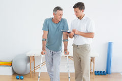 Therapist discussing reports with disabled patient in gym hospital. Male therapist discussing reports with a disabled patient in the gym at hospital Royalty Free Stock Image