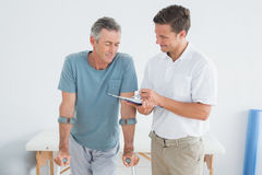 Therapist discussing reports with disabled patient in gym. Male therapist discussing reports with a disabled patient in the gym at hospital Stock Photo