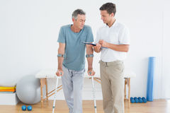 Therapist discussing reports with a disabled patient. Male therapist discussing reports with a disabled patient in the gym at hospital Stock Photography