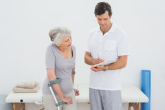 Therapist discussing reports with a disabled senior patient. Male therapist discussing reports with a disabled senior patient in the gym at hospital Stock Image