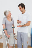 Therapist discussing reports with a disabled senior patient. Male therapist discussing reports with a disabled senior patient in the gym at hospital Stock Photo