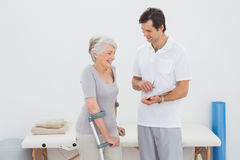Therapist discussing reports with a disabled senior patient. Male therapist discussing reports with a disabled senior patient in the gym at hospital Stock Photography