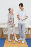 Therapist discussing reports with a disabled senior patient. Male therapist discussing reports with a disabled senior patient in the gym at hospital Stock Photos