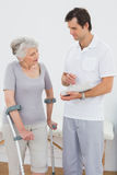 Therapist discussing reports with a disabled senior patient. Male therapist discussing reports with a disabled senior patient in the gym at hospital Royalty Free Stock Images