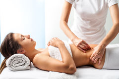 Therapist doing healing massage on female abdomen. Royalty Free Stock Images
