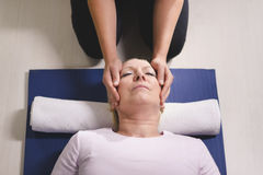 Therapist doing reiki therapy to senior woman Stock Photo