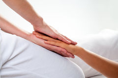 Therapist doing reiki treatment on girls hand. Stock Images