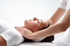 Therapist doing reiki on woman's neck. Close up portrait of young woman at reiki session.Therapist touching woman's neck wit hands stock photography