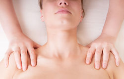 Therapist doing shoulders massage. And pressing points to release tension in levator scapulae muscle stock image