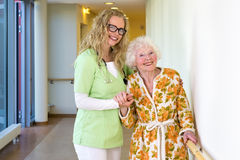 Therapist and Elderly Patient Smiling at Camera. Kind Young Female Therapist and her Elderly Woman Patient Smiling at the Camera at the Corridor Inside the Royalty Free Stock Photography