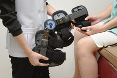 Therapist fitting a knee brace to patient knee in rehab. Physical therapist fitting a knee brace to patient knee in rehab center Royalty Free Stock Images