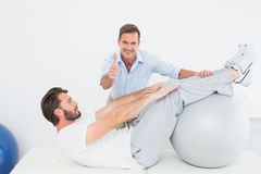 Therapist gestures thumbs up while assisting man do sit ups Royalty Free Stock Images