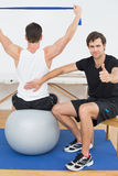 Therapist gestures thumbs up besides man on yoga ball Royalty Free Stock Photos