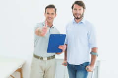 Therapist gesturing thumbs up with disabled patient Royalty Free Stock Images