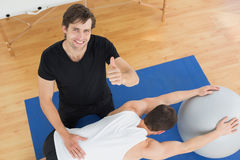 Therapist gesturing thumbs up by man with yoga ball Royalty Free Stock Image
