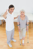Therapist gesturing thumbs up with senior disabled patient. High angle portrait of a male therapist gesturing thumbs up with senior disabled patient in the Stock Images