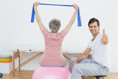 Therapist gesturing thumbs up by woman on yoga ball Stock Photo