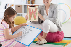 Therapist and girl drawing letter Royalty Free Stock Photo