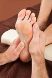 Therapist giving foot massage to female customer at spa Stock Photo