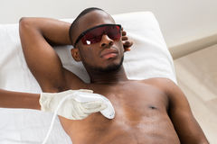 Therapist Giving Laser Epilation On Man's Chest Royalty Free Stock Photography