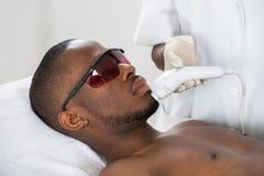 Therapist Giving Laser Epilation Treatment On Young Man. Close-up Of Therapist Giving Laser Epilation Treatment On Young African Man royalty free stock image
