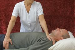 Therapist giving Polarity Therapy Treatment. Male client lying on couch with female healing therapist channeling healing Stock Image